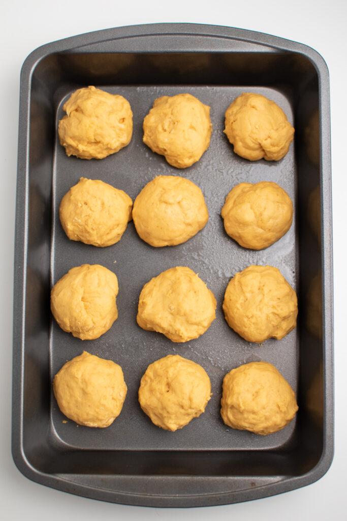 Pumpkin dough balls in a cake pan.