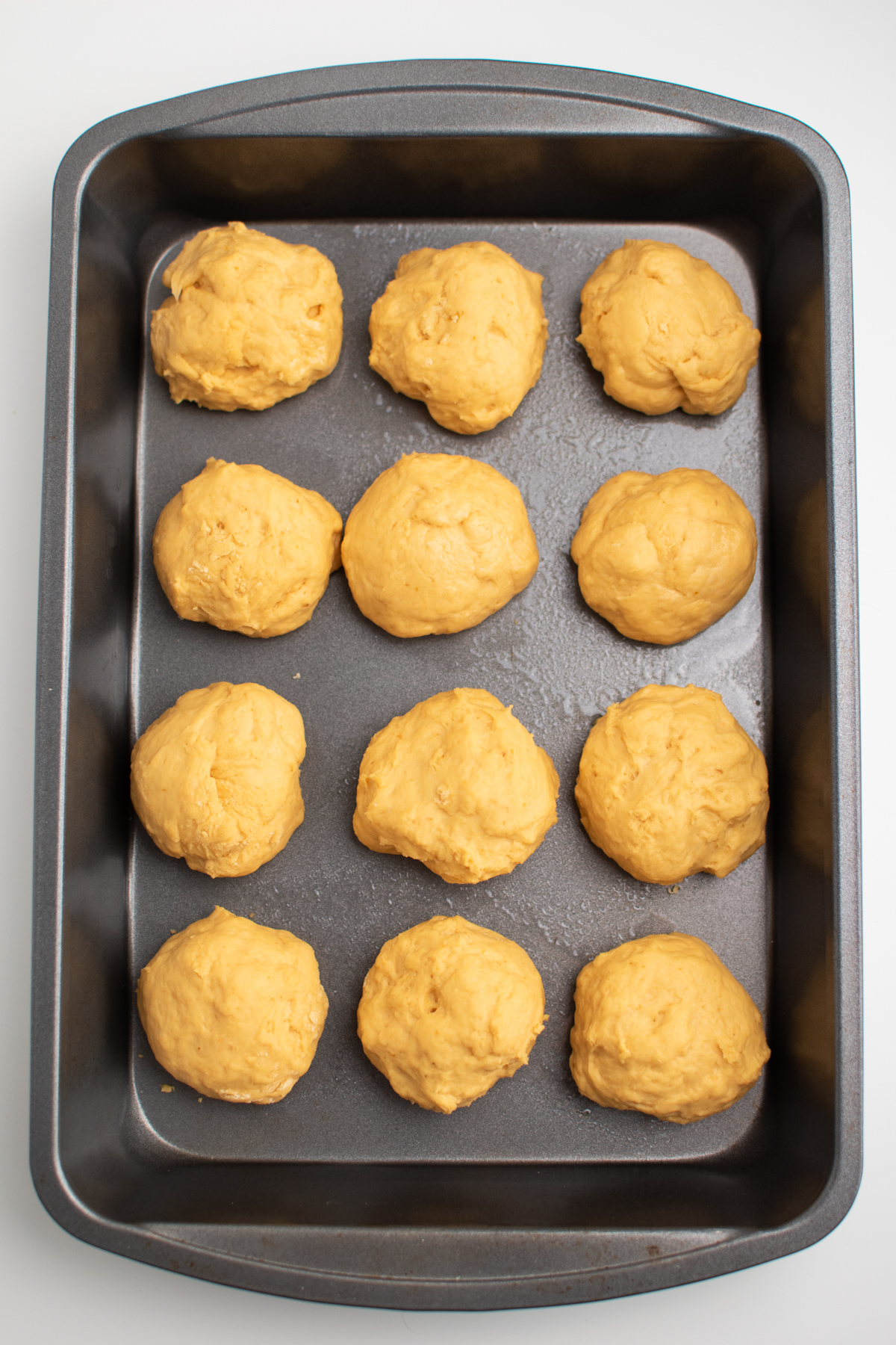 12 uncooked pumpkin dough balls in a greased cake pan.