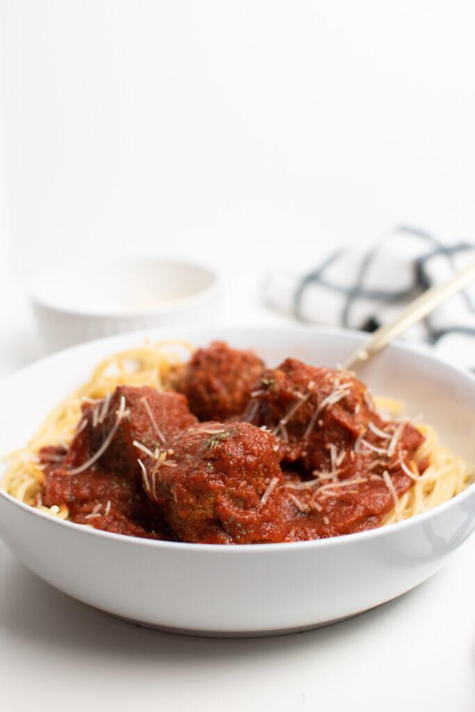 Spaghetti and meatballs in a white dish.