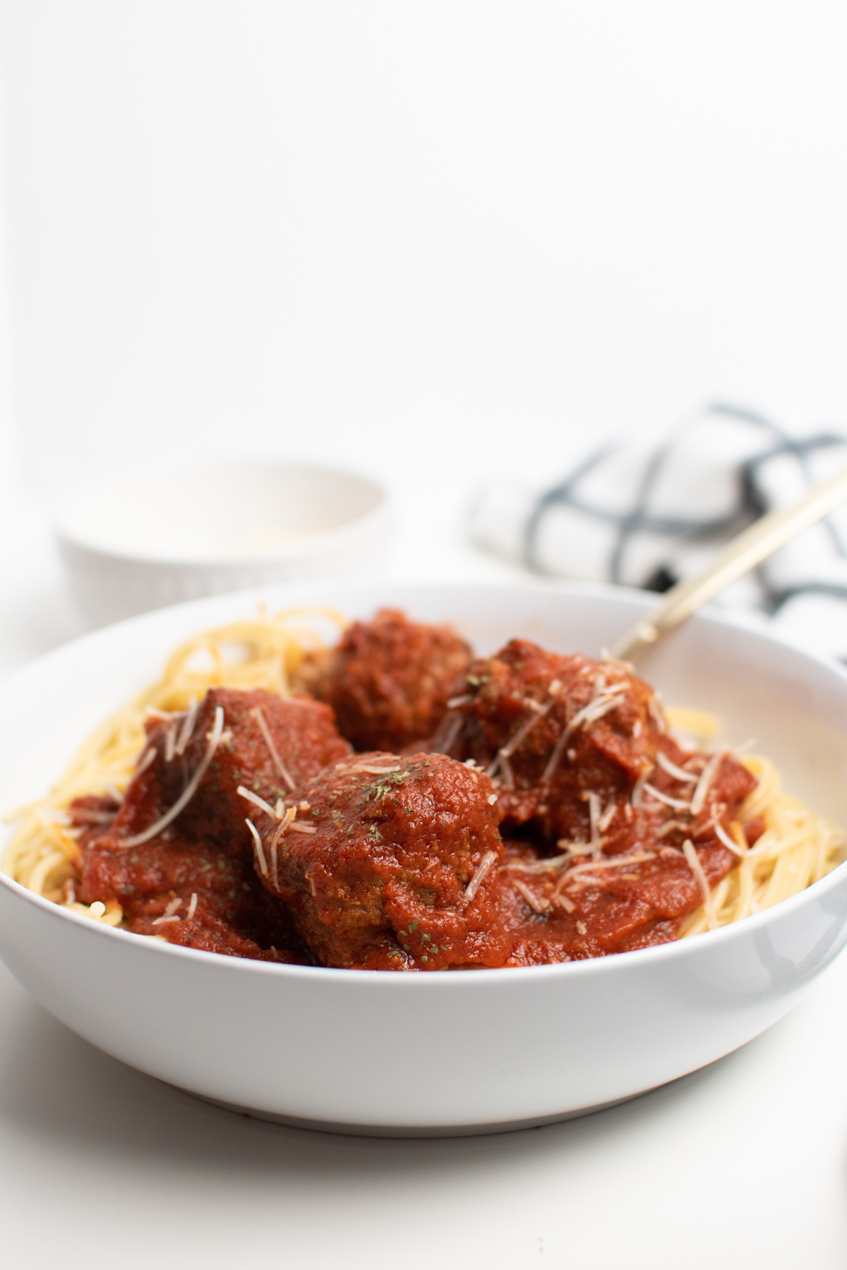 Spaghetti and meatballs in a white bowl on white table.