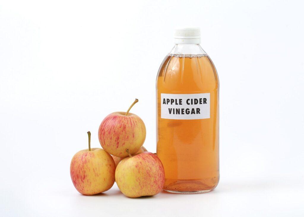 Apple cider vinegar in glass jar next to stack of apples.