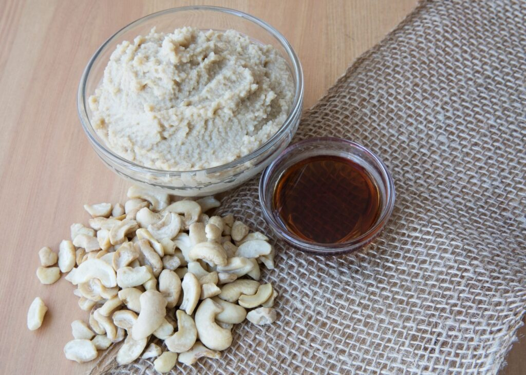 Cashew cream in glass bowl next to nuts and oil.