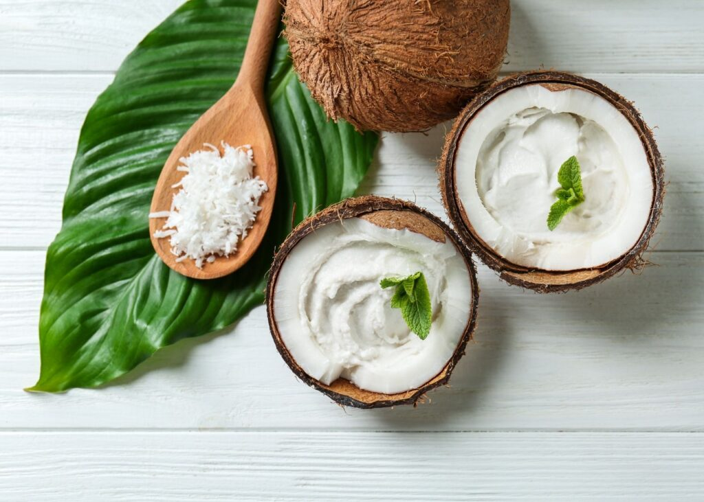 Coconut cream in coconut shells next to leaf.