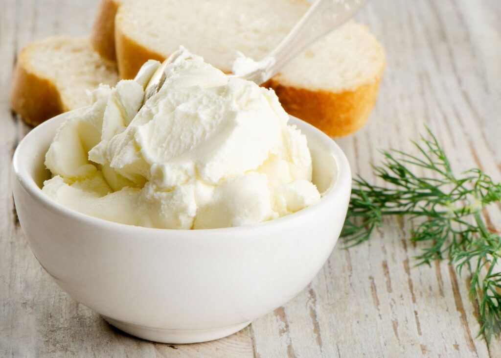 Cream cheese in white bowl next to bread and garnish.