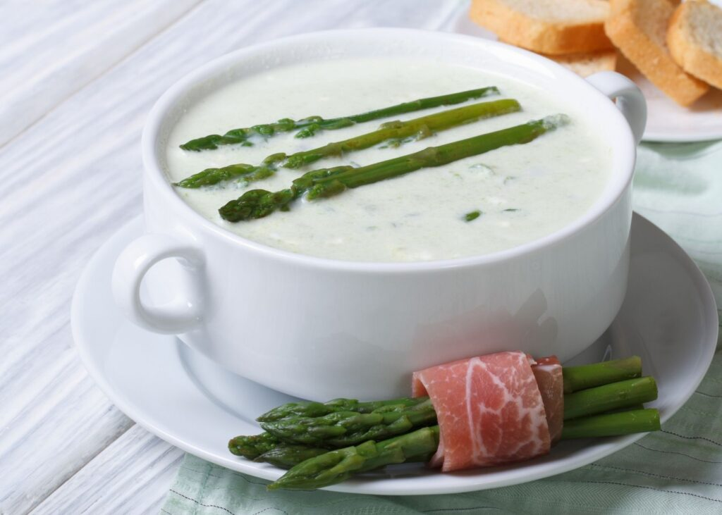Cream of asparagus soup topped with asparagus spears in white bowl.
