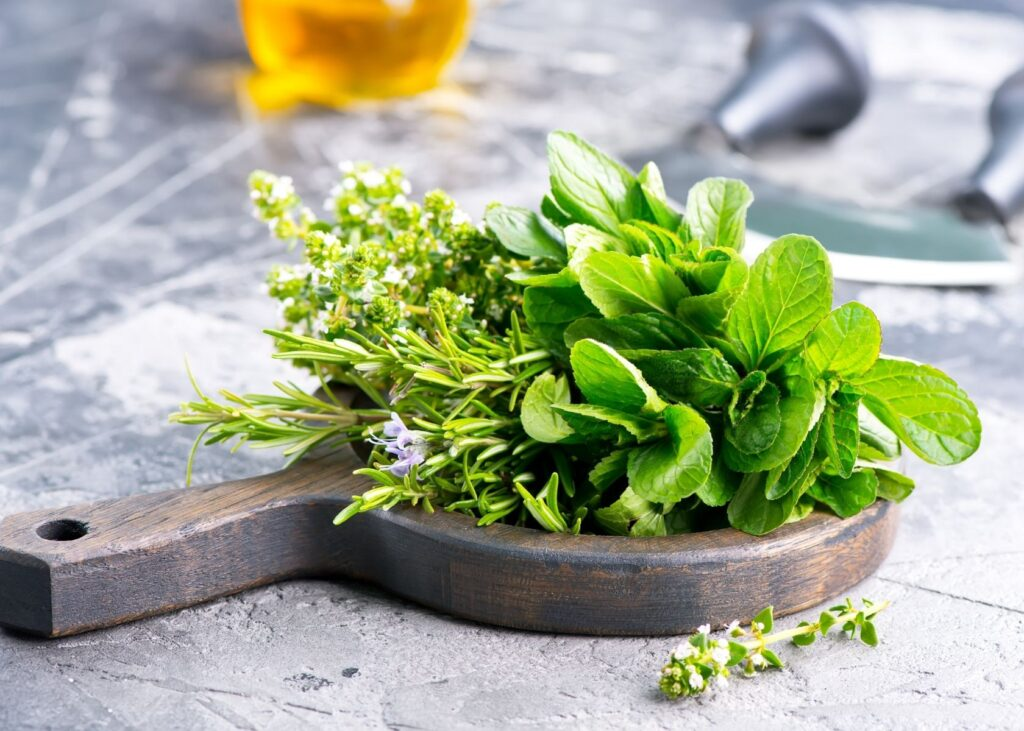 Fresh herbs on rustic wooden tray.