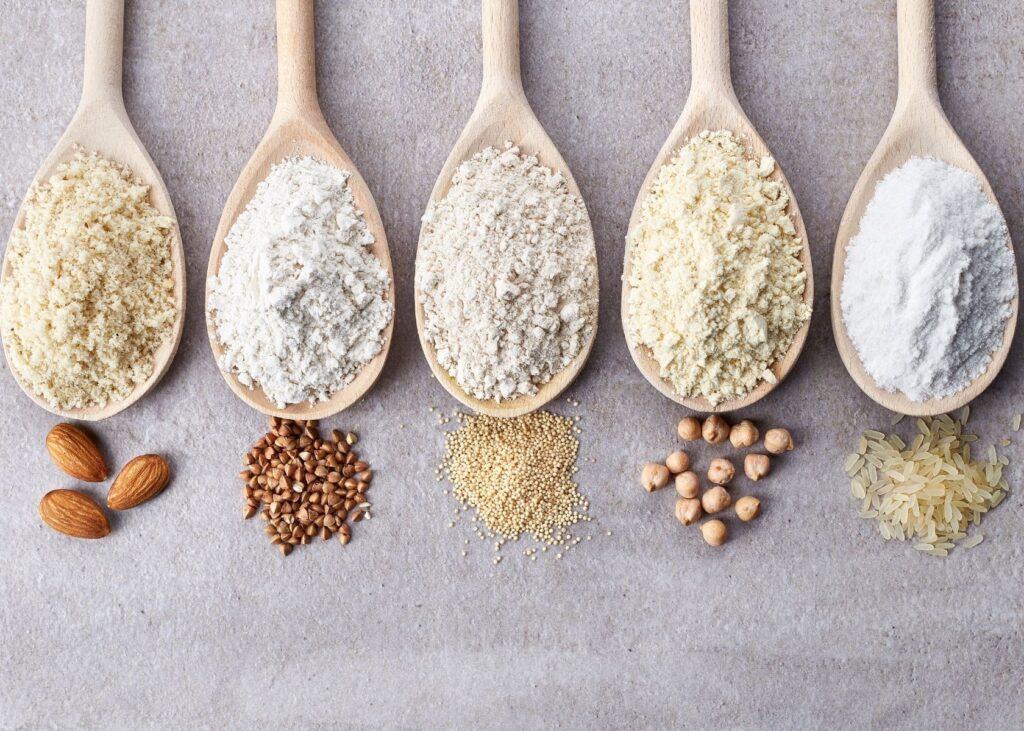 Gluten free flour varieties on wooden spoons.