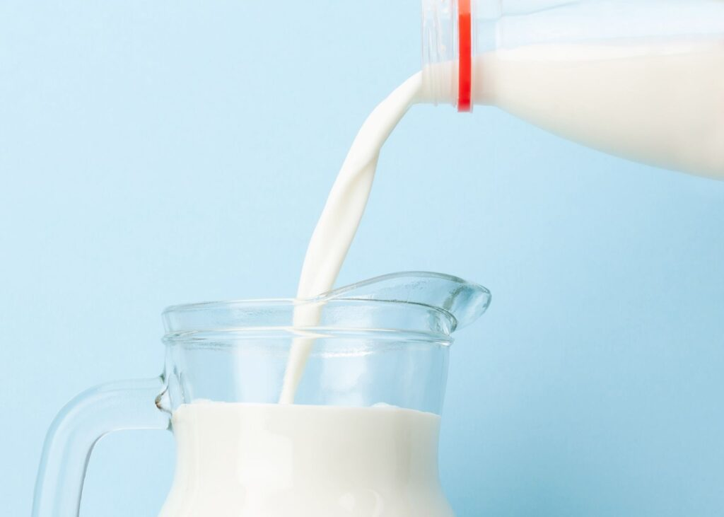 Milk is poured from the jug to a glass pitcher.