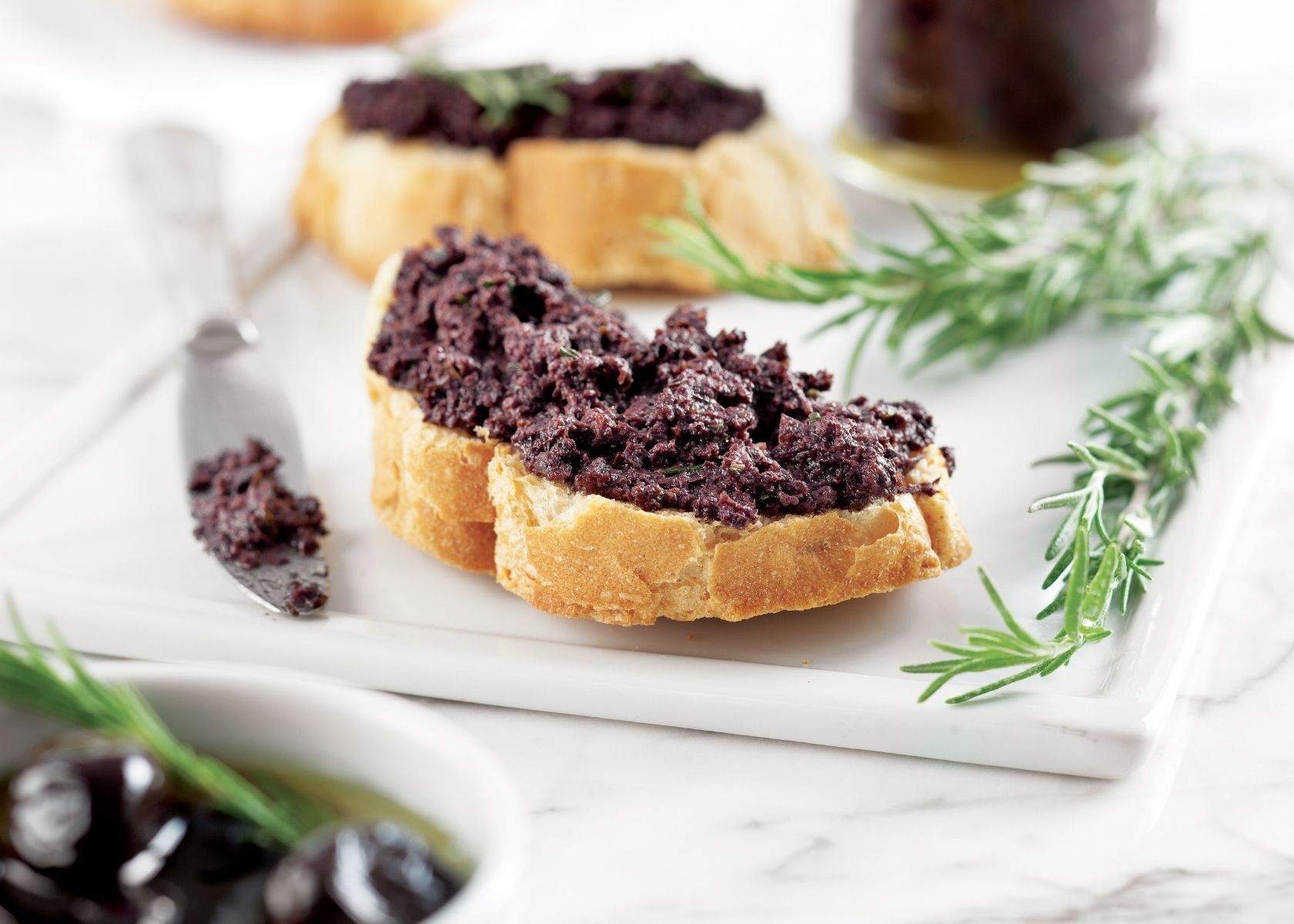 Toast with pureed olives on top next to sprigs of thyme all on white plate.