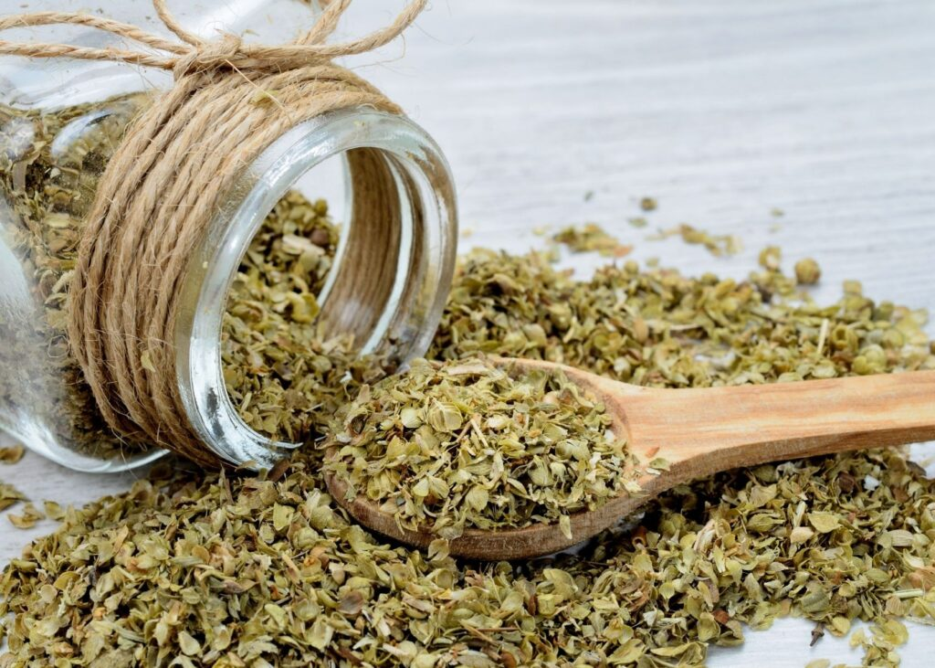 Dried oregano spills out of glass jar with wooden spoon.