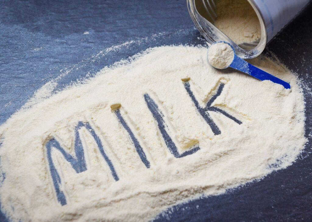 """""""Milk"""" written in powdered milk on counter."""