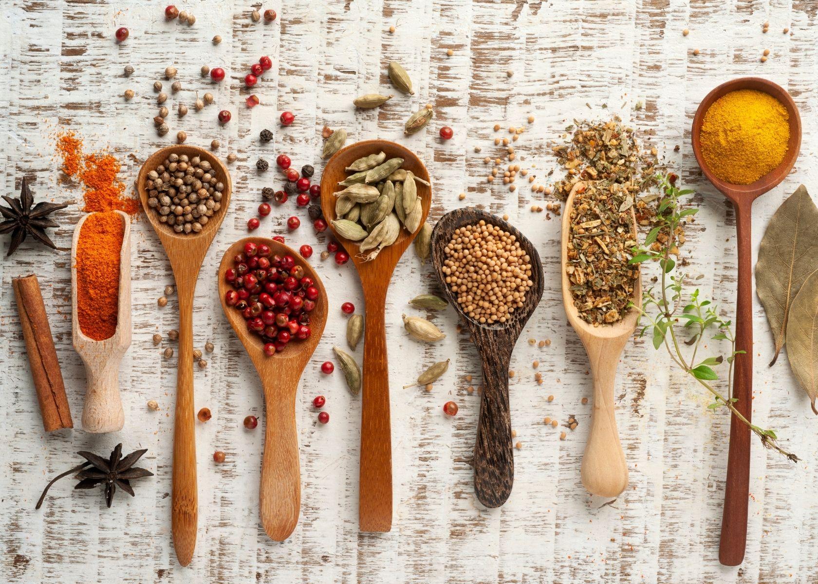 Various seasonings in lined up wooden spoons with some seasoning sprinkled on table.