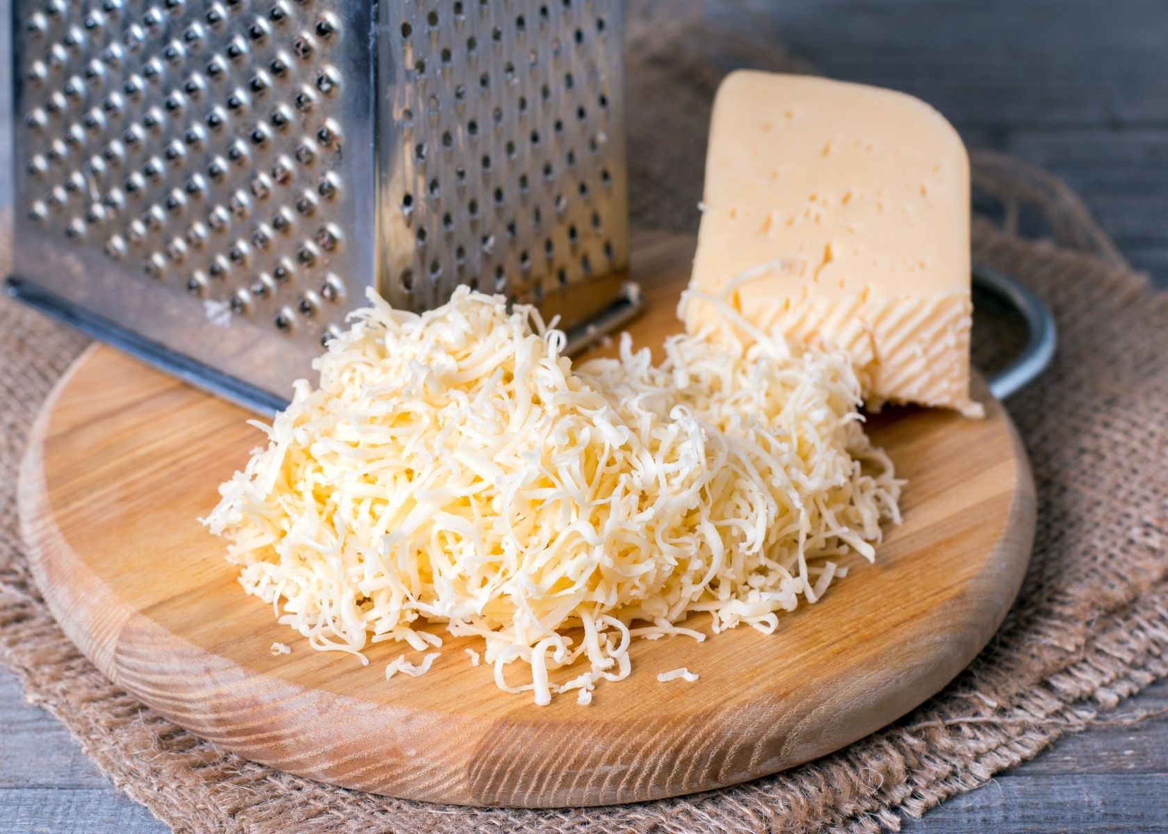 Grated cheese on wooden circle next to block and metal grater.