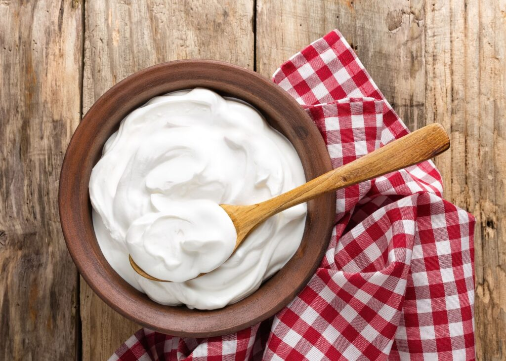 Sour cream in wooden bowl with red plaid kitchen towel.