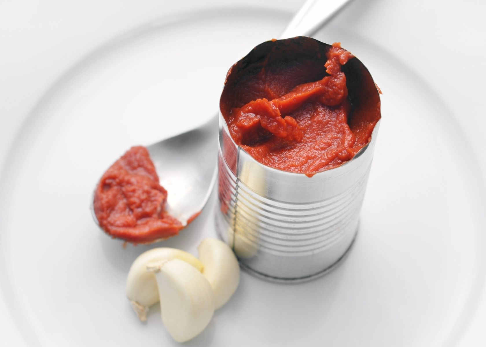 Tomato paste in open tin can next to garlic cloves and spoon covered in the paste.