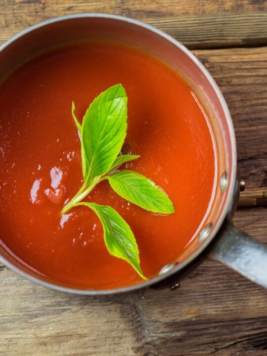 Tomato sauce in metal sauce pan over a rustic wooden table with green garnish.
