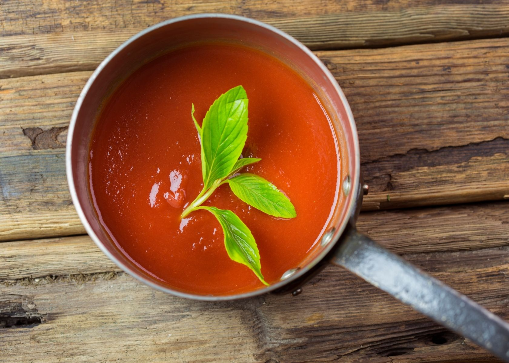 Tomato sauce in sauce pan with basil leaf stem on top sits on wood table.