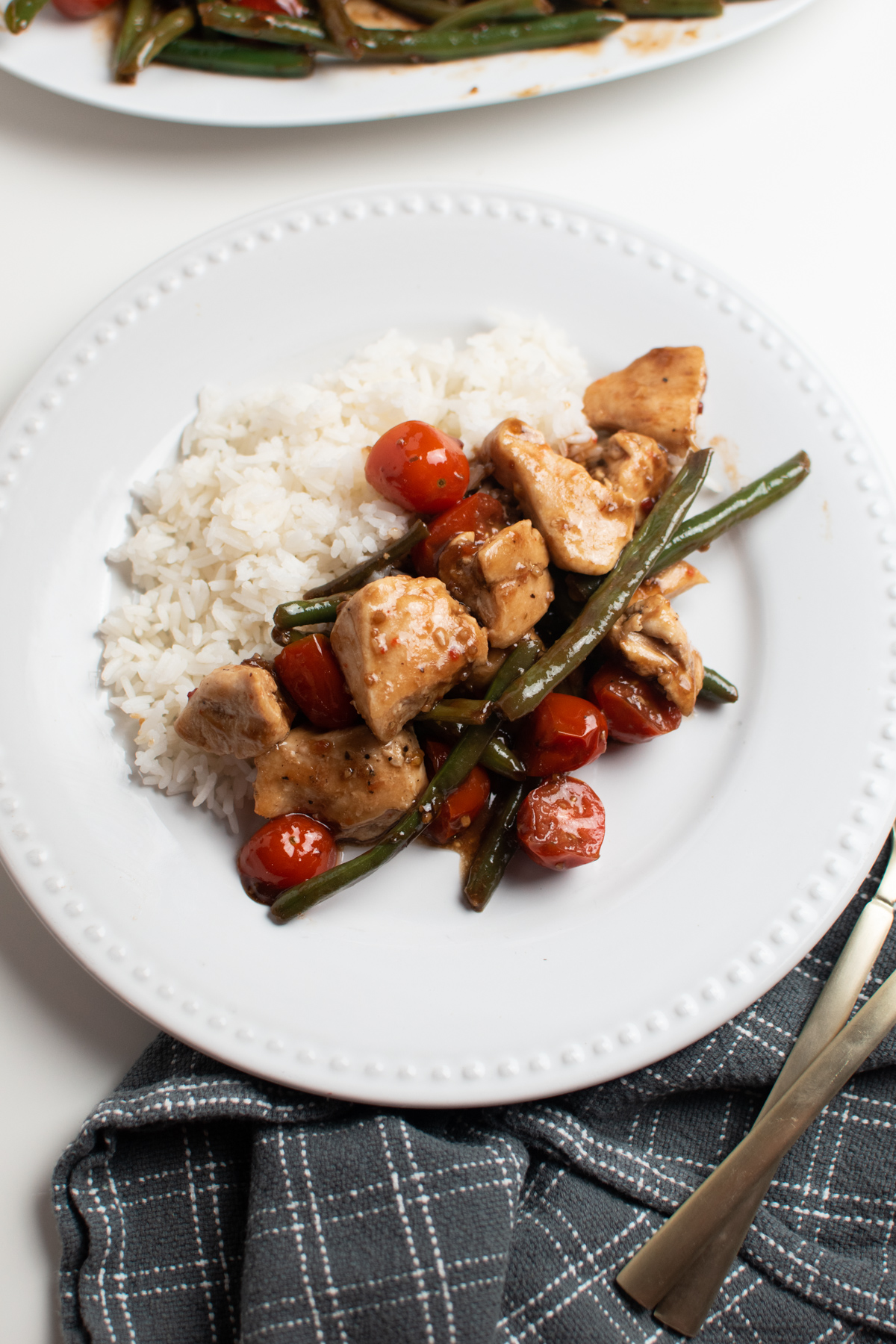 White plate of balsamic chicken, green beans, and cherry tomatoes next to rice.