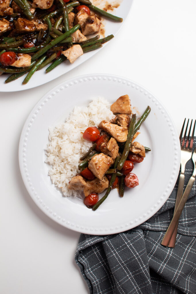 White plate with rice and balsamic chicken with tomatoes.