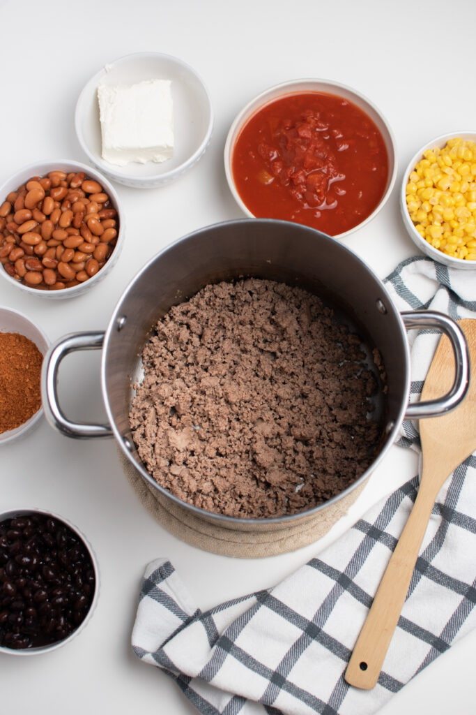 Browned ground beef in a pot surrounded by bowls of ingredients.