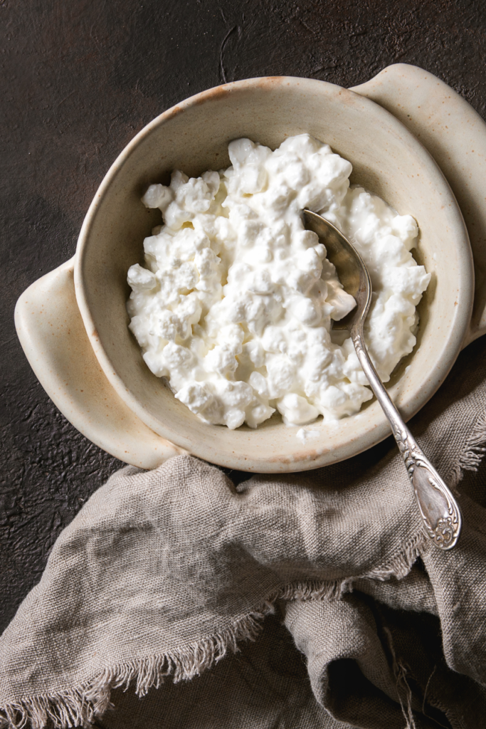 A bowl of cottage cheese with a spoon in it.