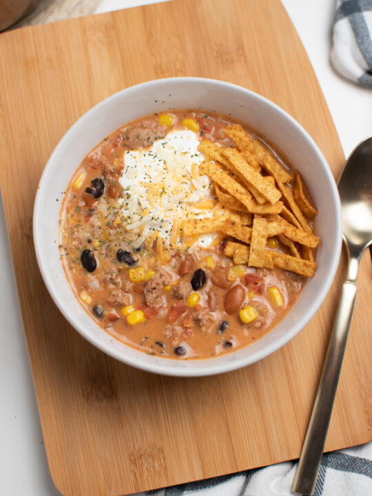 Creamy taco soup in a bowl on a cutting board.