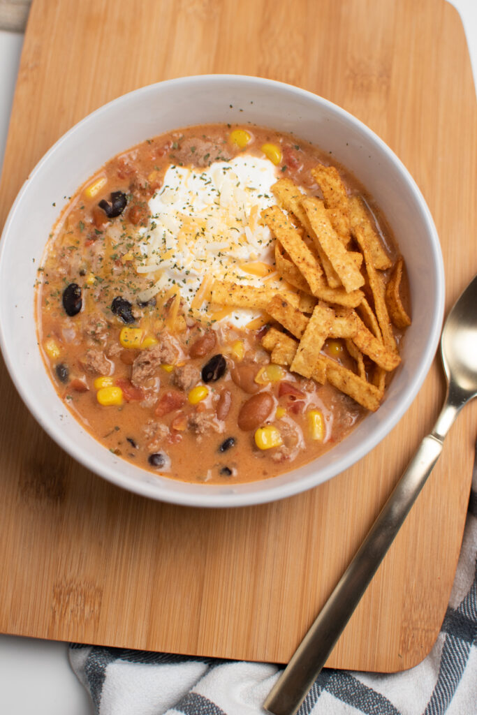 Bowl of taco soup on a cutting board.