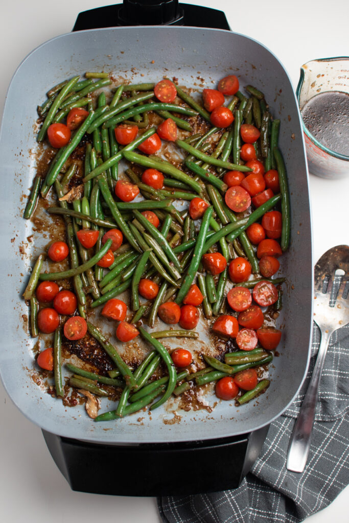 Green beans and tomatoes in a skillet.
