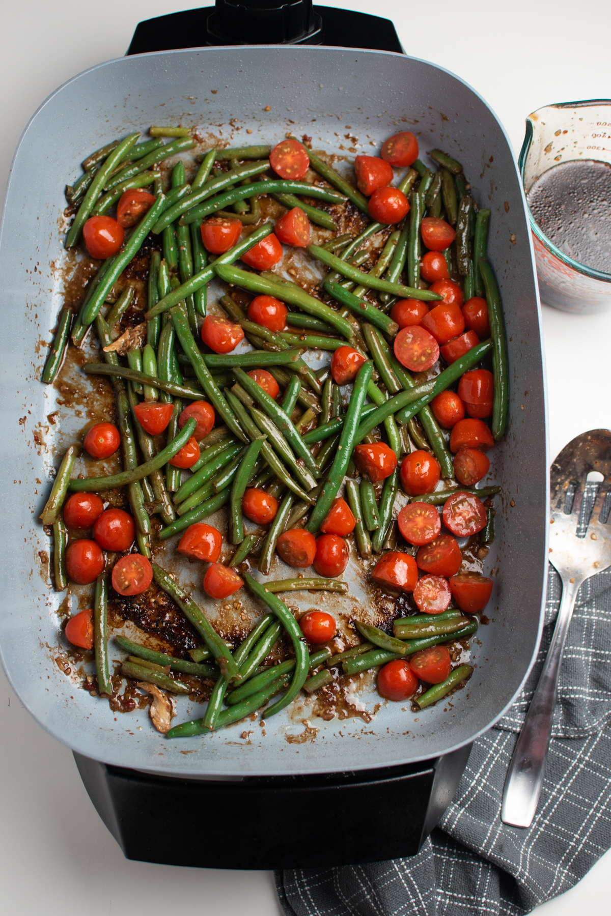 Several cooked green beans and sliced cherry tomatoes in electric skillet.