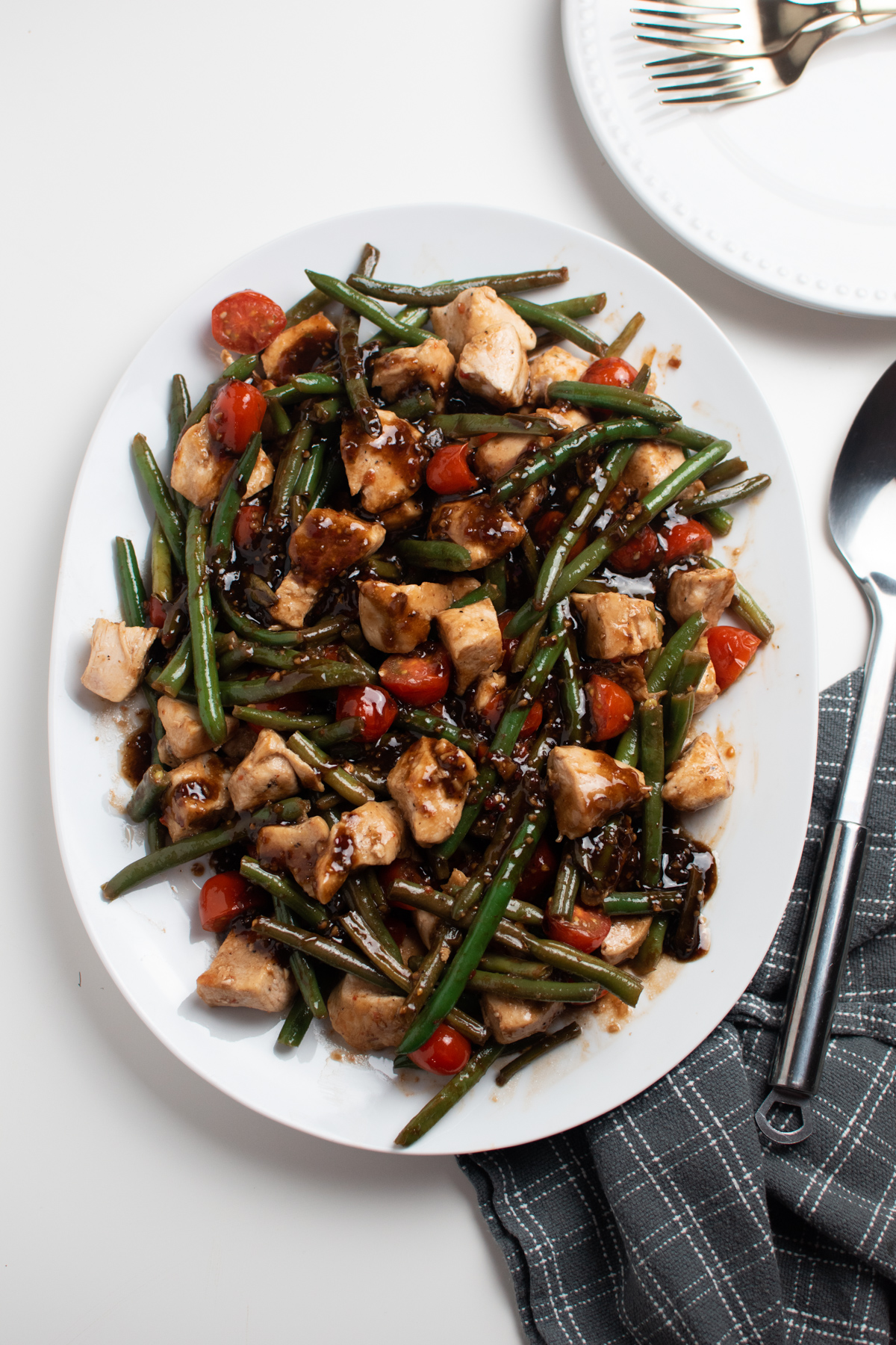 White platter of balsamic chicken, green beans, and cherry tomatoes next to gray towel.