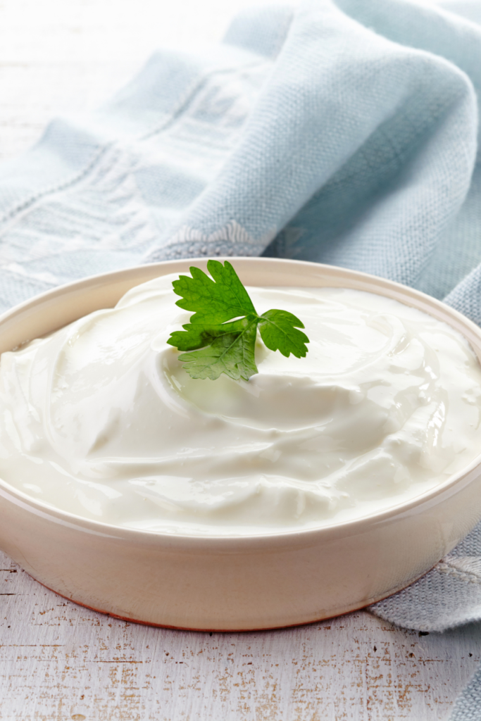A bowl of sour cream with some parsley on top.