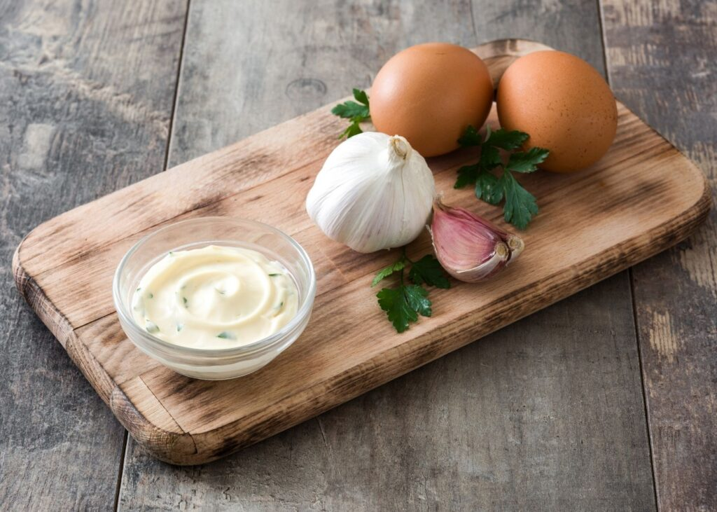 Aioli in clear bowl next to recipe ingredients.