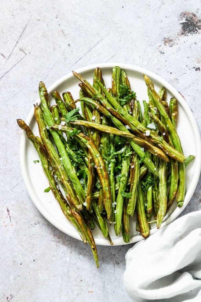 Air fryer green beans on white plate.