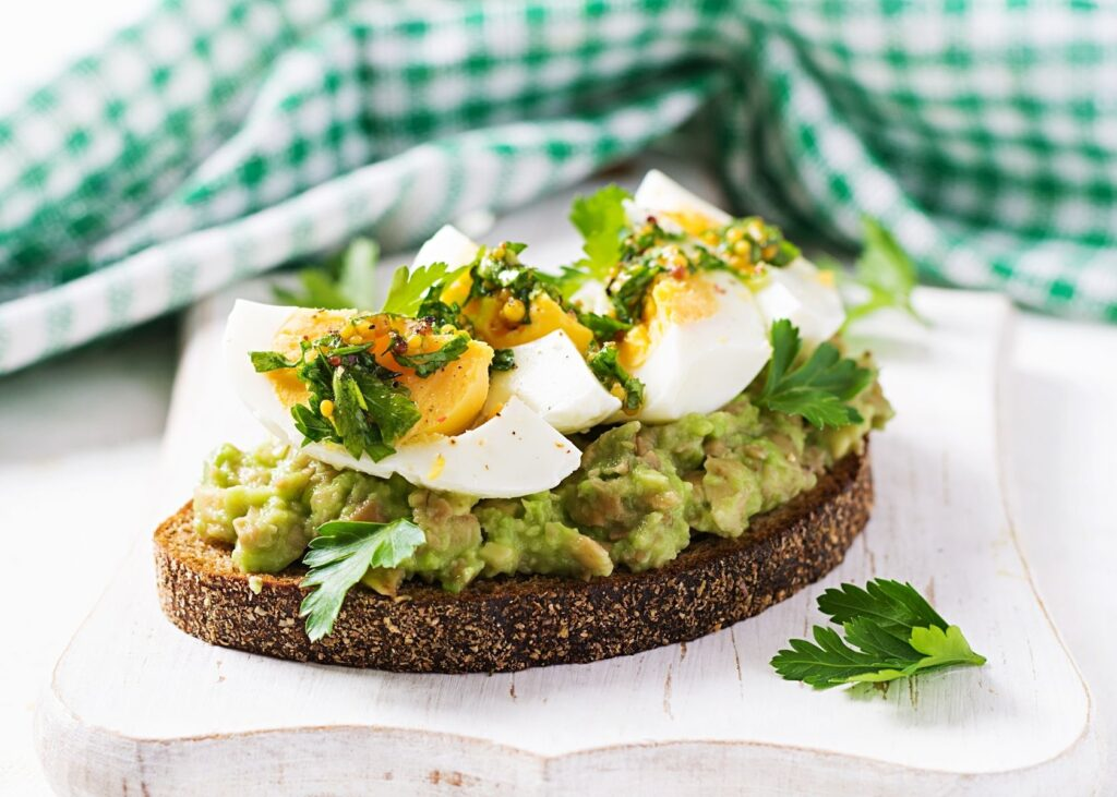 Mashed avocado mayo on bread with boiled egg slices.