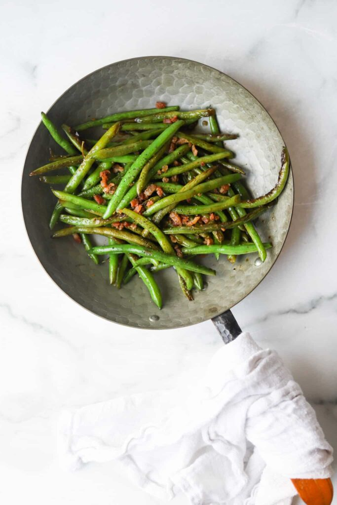 Balsamic green beans with bacon in skillet.
