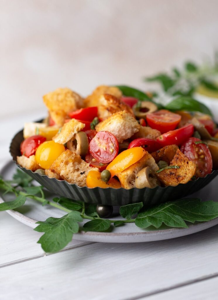 Black dish filled with bread salad.