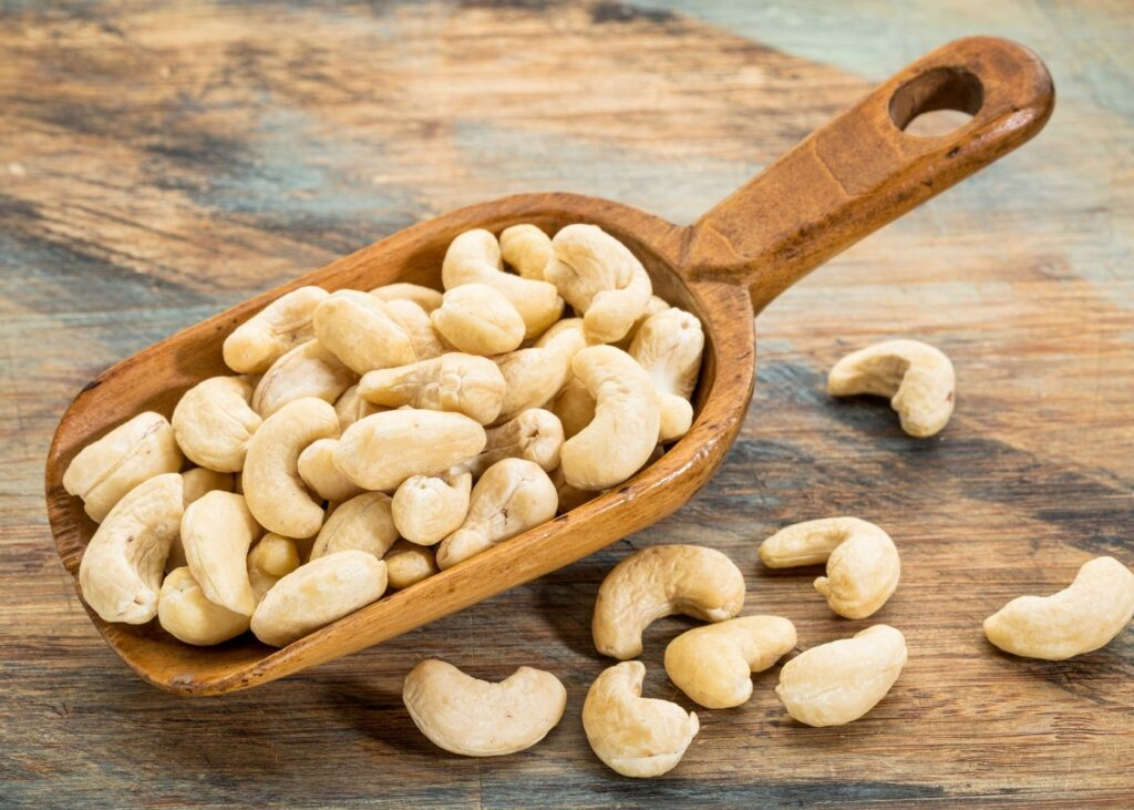 Cashew nuts in large wooden spoon.