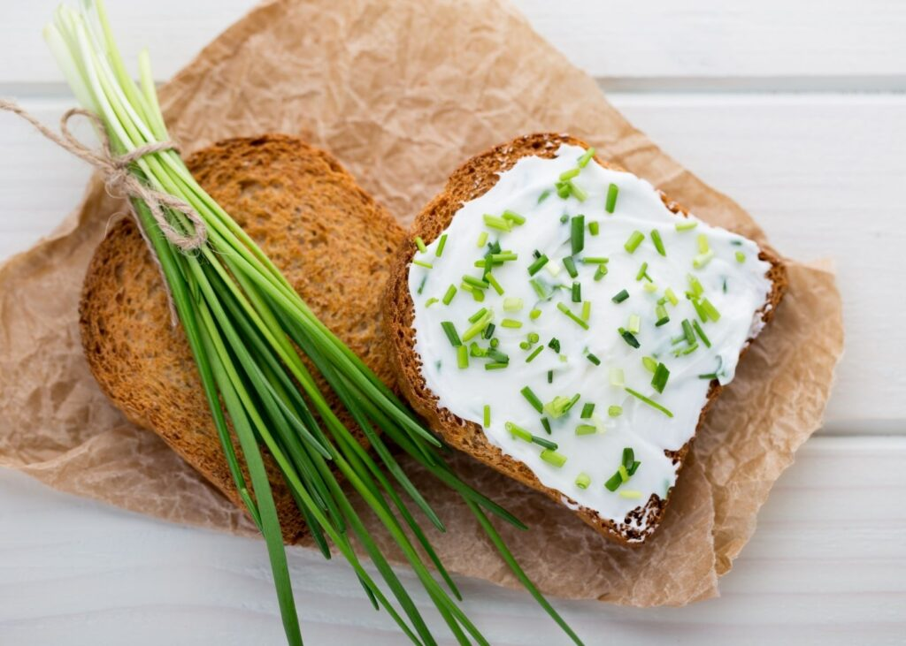 Cream cheese spread on bread with chive garnish.