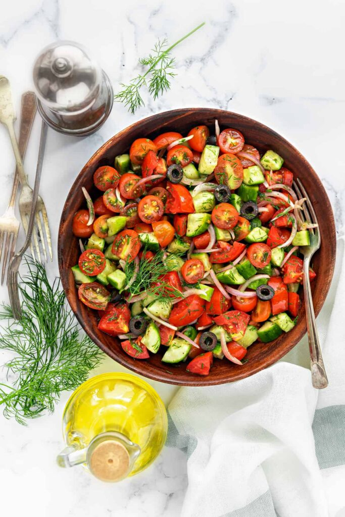 Large bowl of cucumber and tomato salad.
