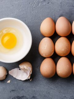 Several eggs lined up next to cracked egg in bowl.