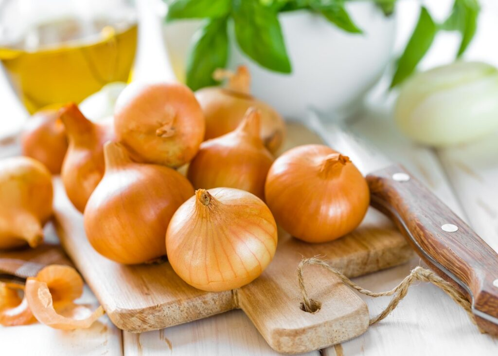 Several onions stacked on rustic wooden cutting board.