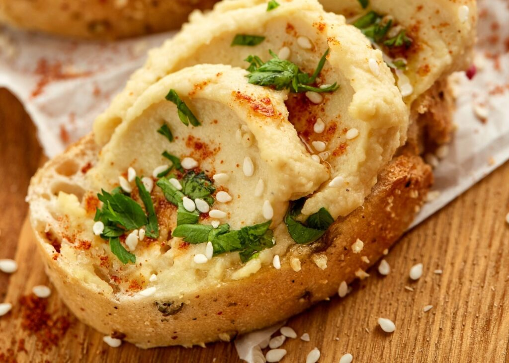 Hummus spread on bread with garnish.