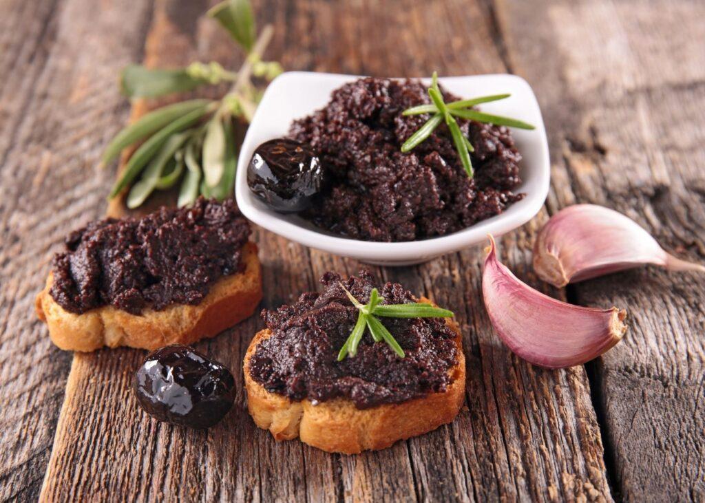 Olive spread on toast with garnish.