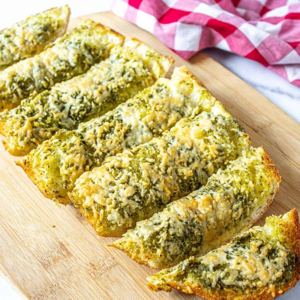 Pieces of pesto garlic bread on cutting board.