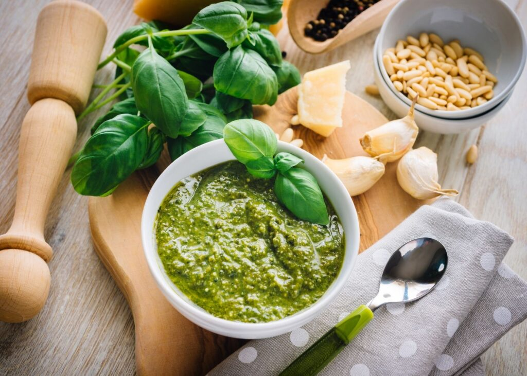 Pesto sauce in white bowl surrounded by ingredients.