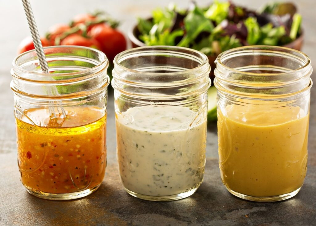 3 different salad dressings in glass jars in front of salad.