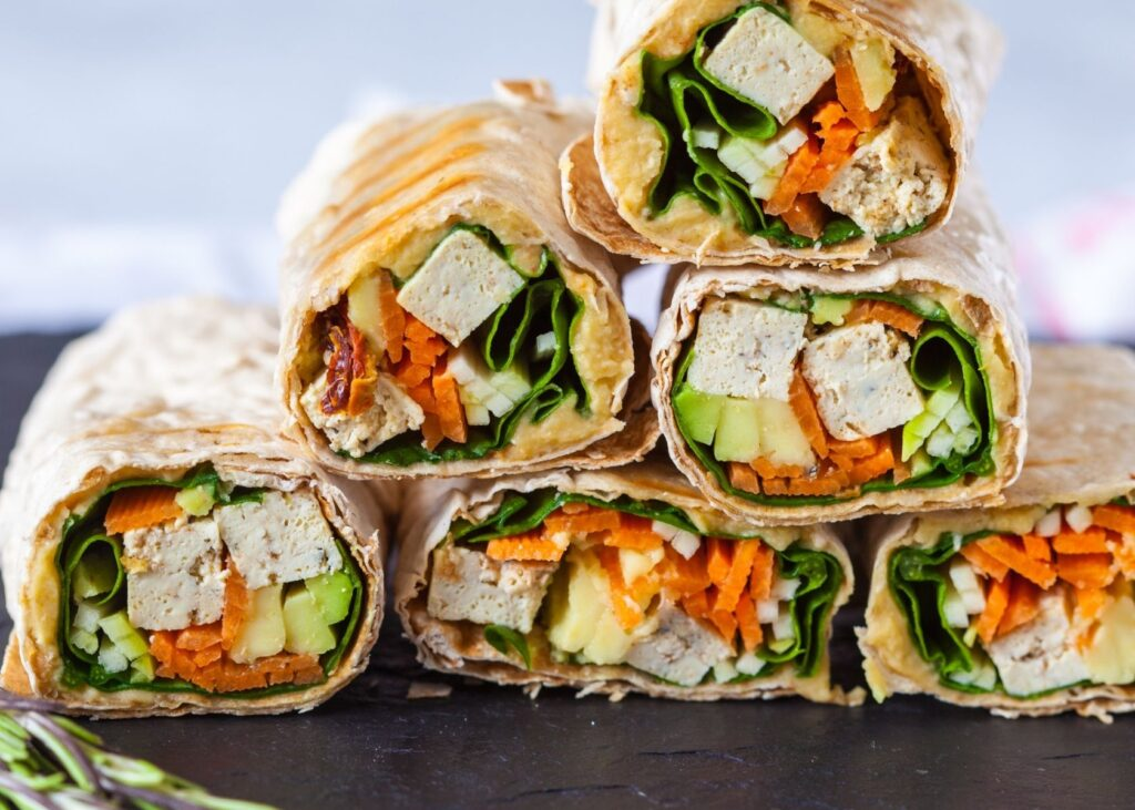 Sandwich wraps with tofu stacked in a pyramid.