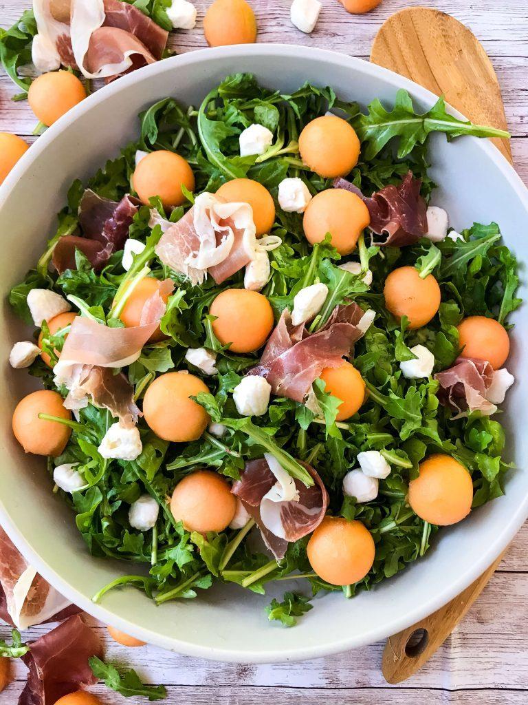 White bowl filled with cantaloupe prosciutto arugula salad.