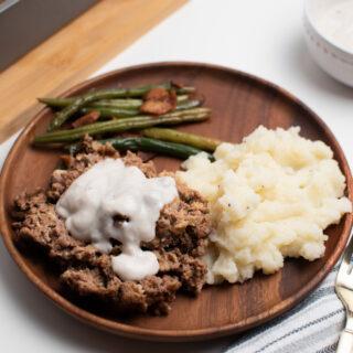 Cream of mushroom meatloaf on a wood plate.