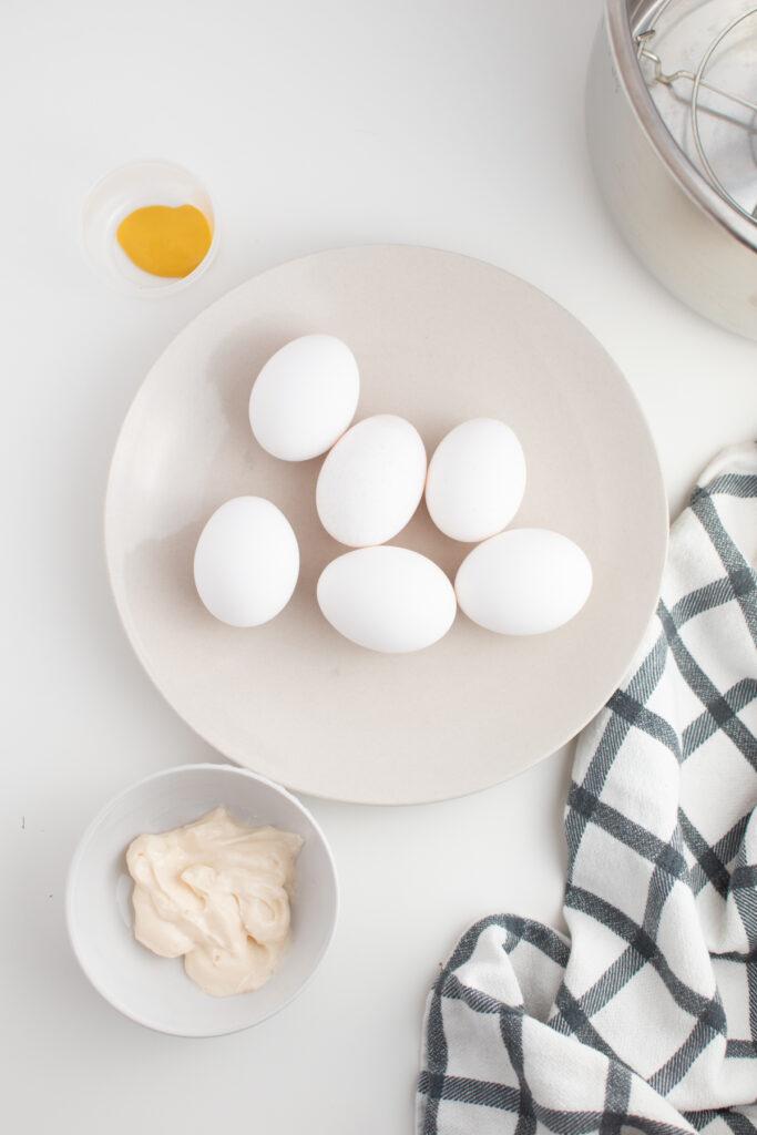 Deviled egg ingredients on white table.